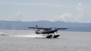 Ein Wasserflugzeug landet und faehrt kurz danach quer durch den Ankerplatz zum Steg des Ressorts.